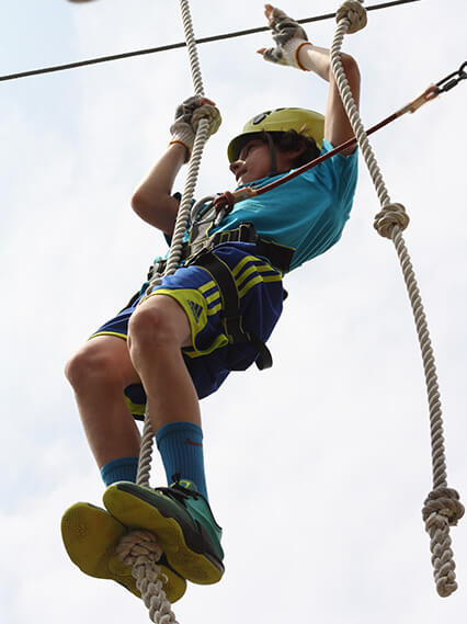 Boy climbing at Wild Blue Ropes Summer Camp