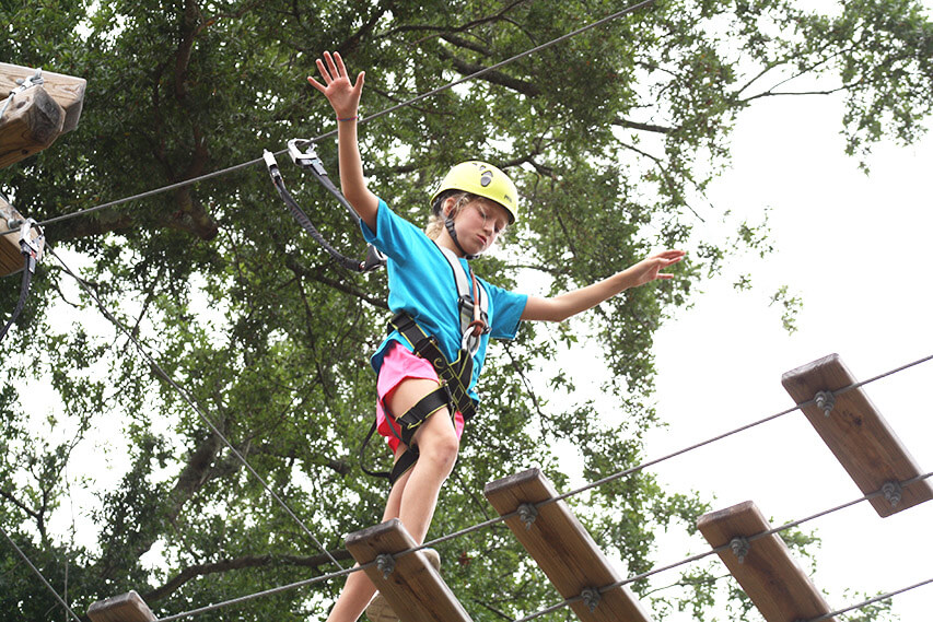 Girl navigating obstacle at Wild Blue Ropes Summer Camp